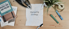 sheet of paper on a wooden table with words marketing strategy on it surrounded by books, pens and a plant
