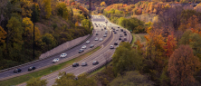 Motorway with cars driving in both directions, surrounded by autumnal trees.
